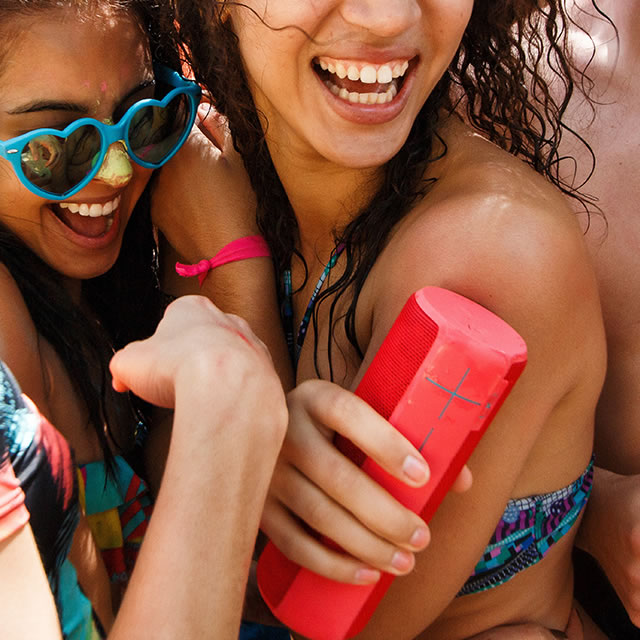 Red UE Boom portable speaker at a beach party