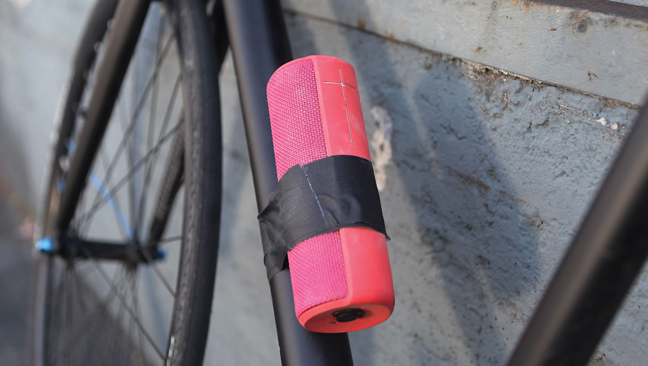 Pink UE Boom portable speaker taped to a bicycle