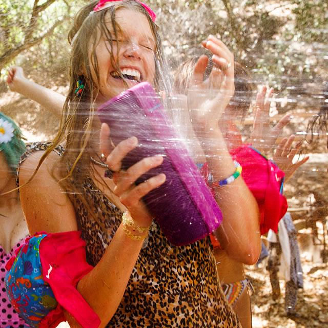 Purple waterproof UE Megaboom mobile speaker splashing