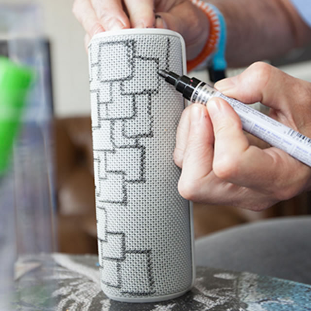 Drawing with markers on a white UE Boom portable speaker